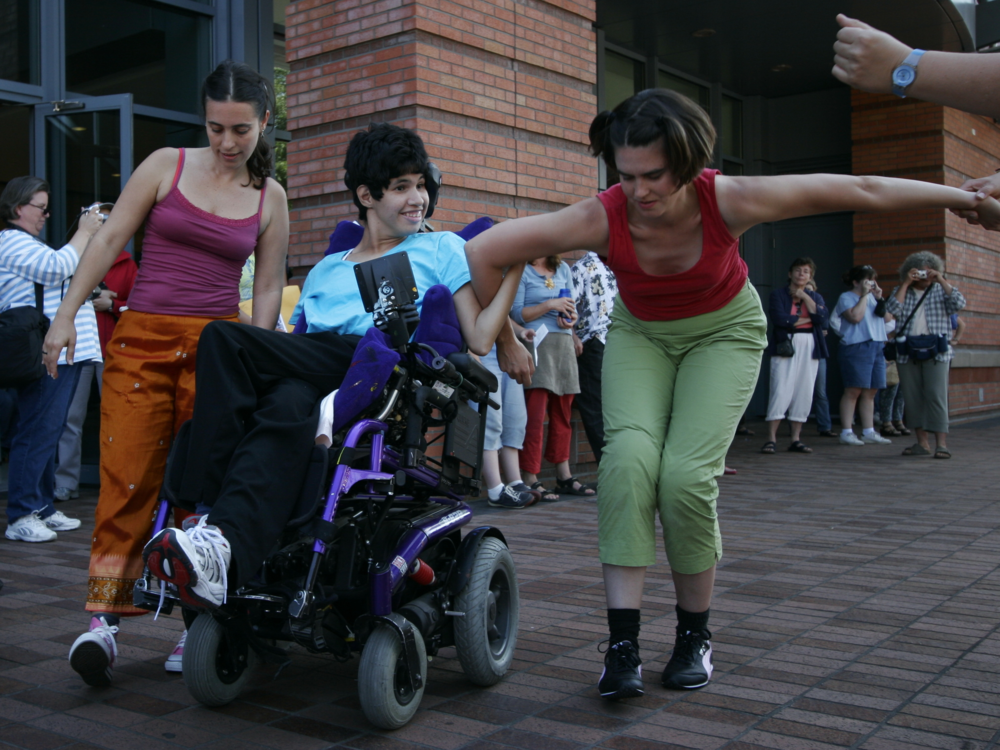 Image: Three mixed ability dancers perform outdoors for a crowd.