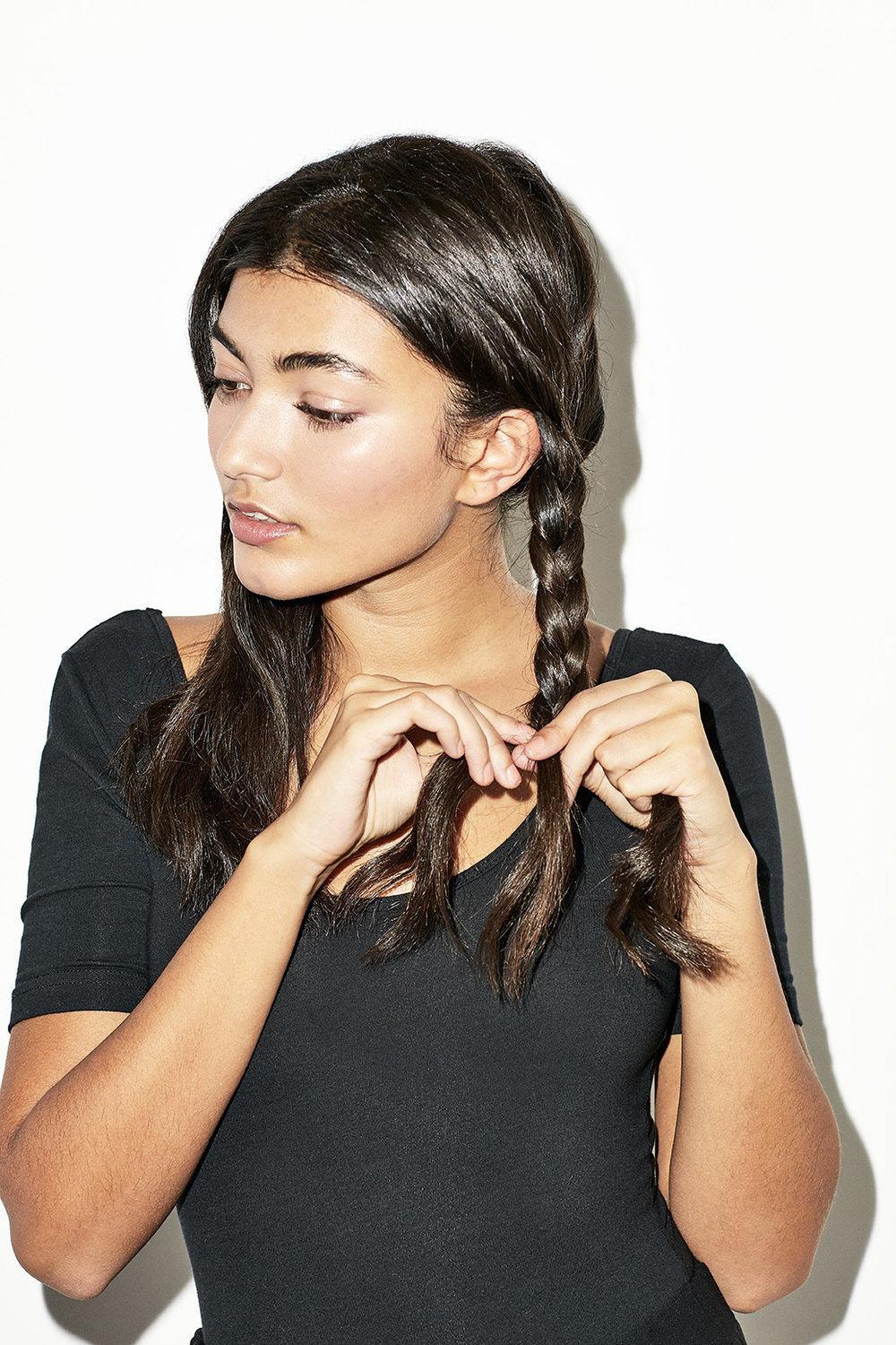 STEP 1 - Create a middle parting down the centre of the head – starting from your nose line as a guide. Now, you have two sections of hair on each side of your head to tie into two ponytails. Separate each ponytail individually into three sections and braid. Then secure with elastic.