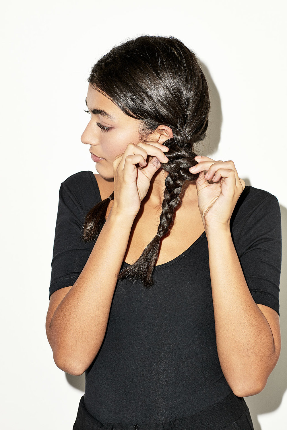STEP 2 - Separate  the braids slightly with your fingers to add a softer texture. Pass the braid over the top of your head to the opposite side and secure with  a grip
