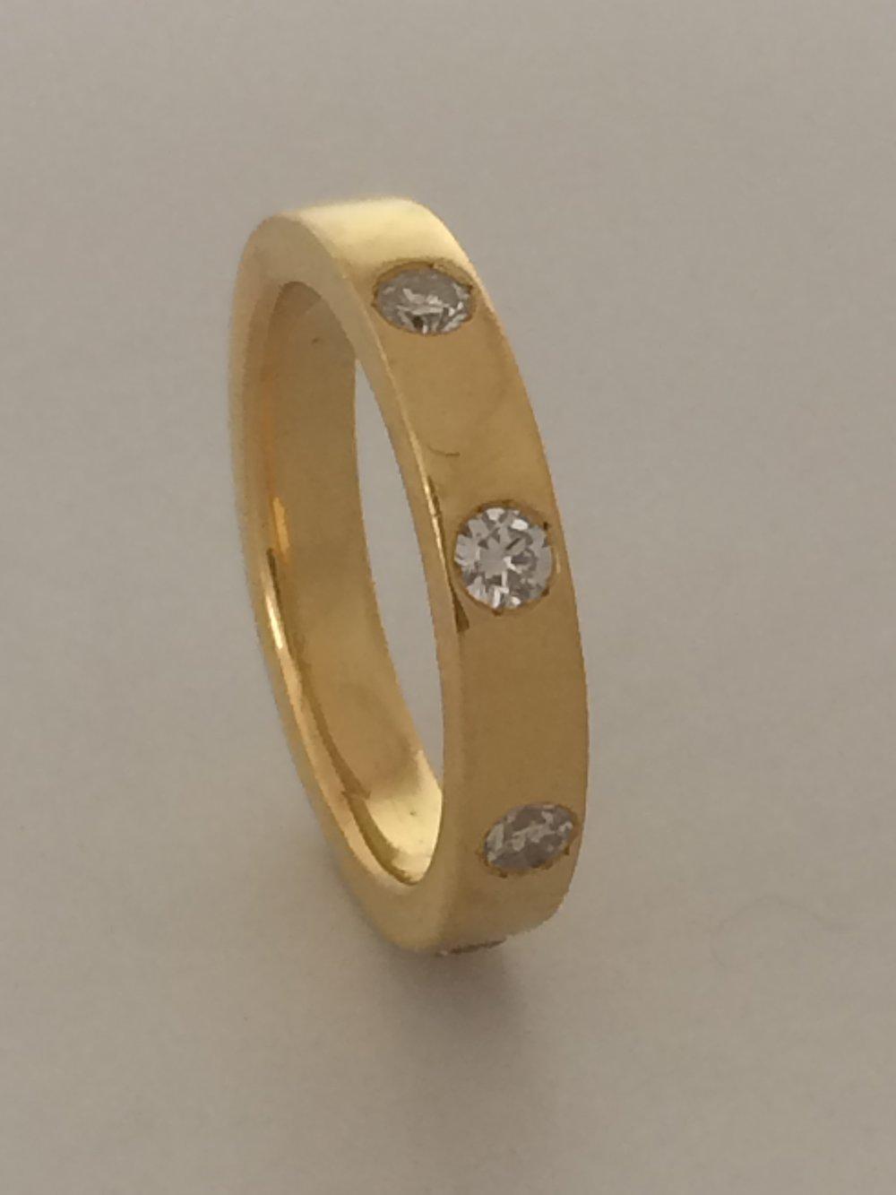 Student's work. 22 karat solid gold band with eight flush set diamonds.