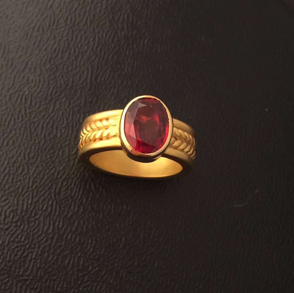 Faceted hessonite garnet set in 22 karat gold twisted wire and half-round band.