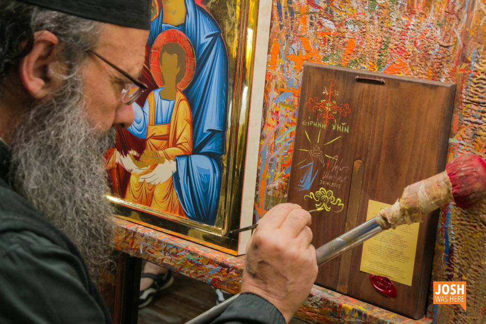 Father Pefkis signs a completed icon