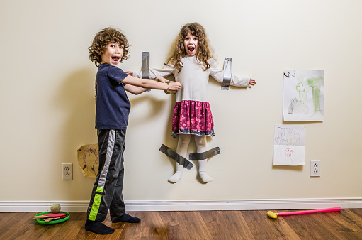 boy taping sister to wall.jpg