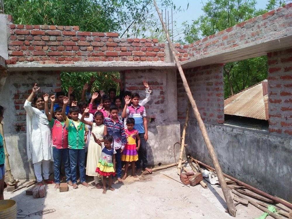 Asha Griha Kids Waving On Roof.jpg