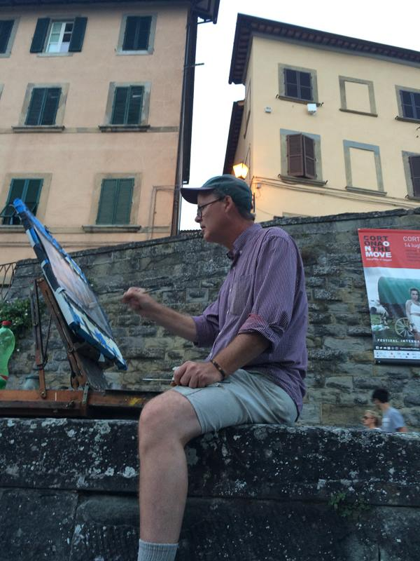sitting on a wall in Cortona, painting...