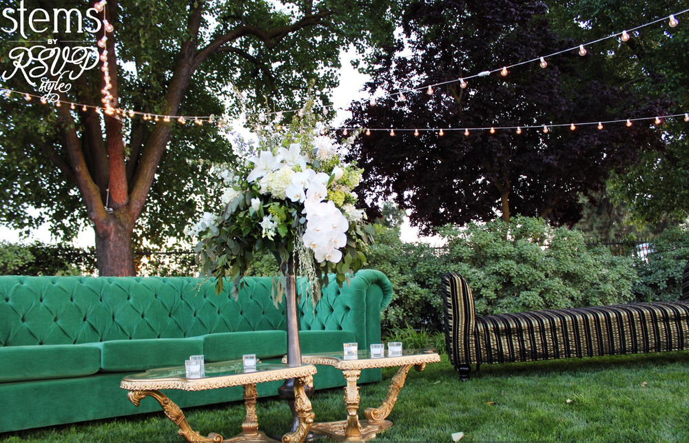 Lounge seating with gold tables and floral arrangements