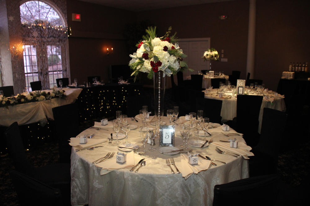 Beautiful tall arrangements on pilsner vase with black headtable skirting and chair covers!  Wow!
