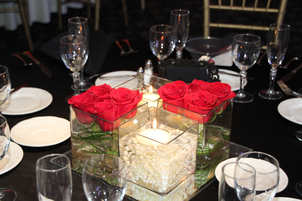 Four square vases on square mirror with pearls and roses