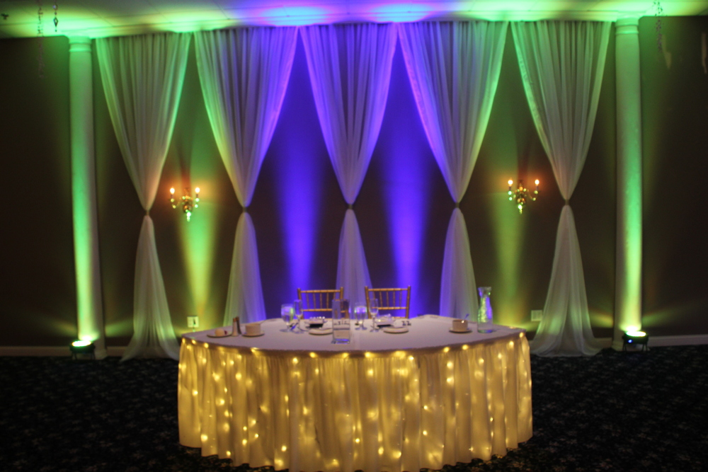 Voile curtains with purple and green uplights behind a sweetheart head table