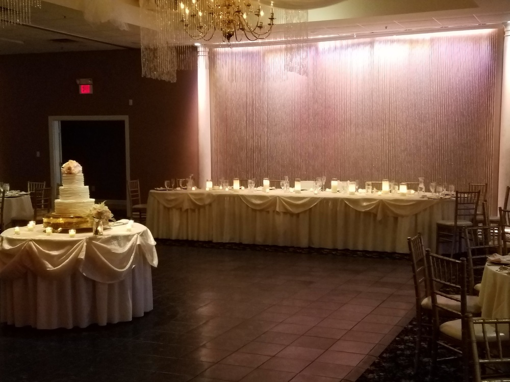 Oval head table (without twinkle lights underneath) with Ivory Bichon tablecloths and crystal curtain backdrop