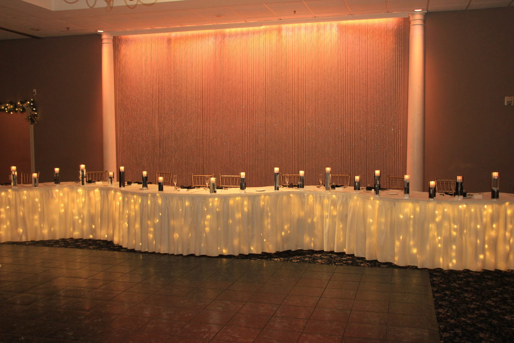 Mirrored candle holders line this headtable with soft pink on crystal curtain backdrop