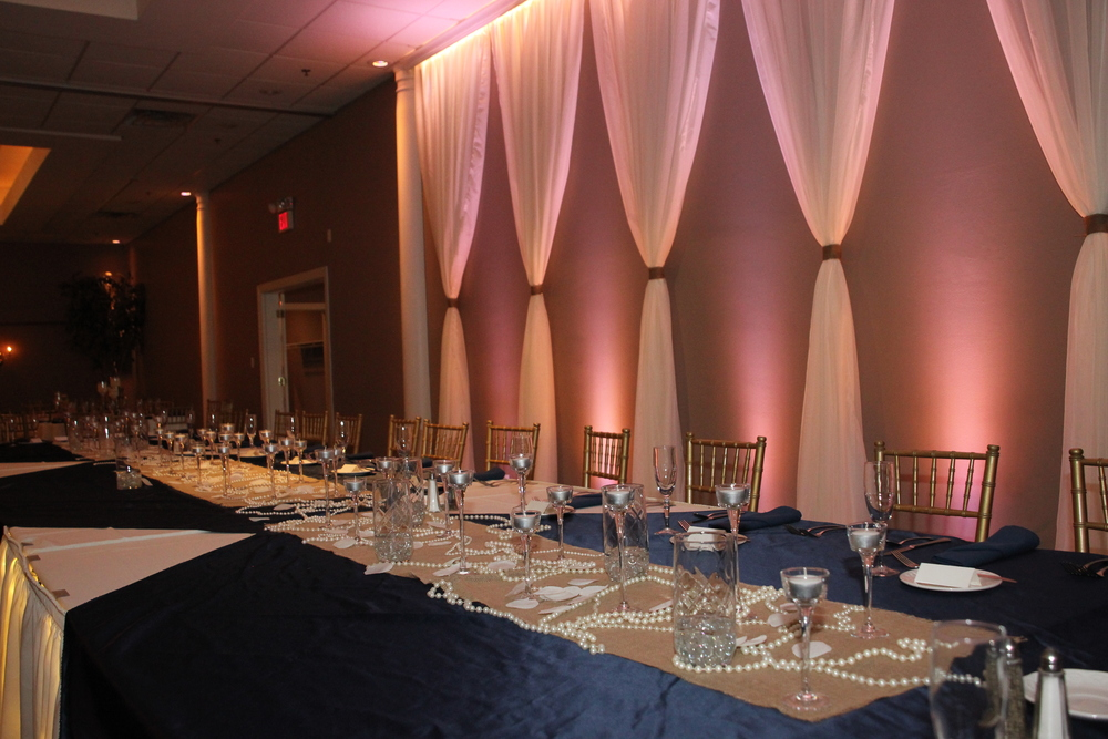 Oval head table with Navy Satin tablecloths and burlap runners and voile curtains with burlap ties