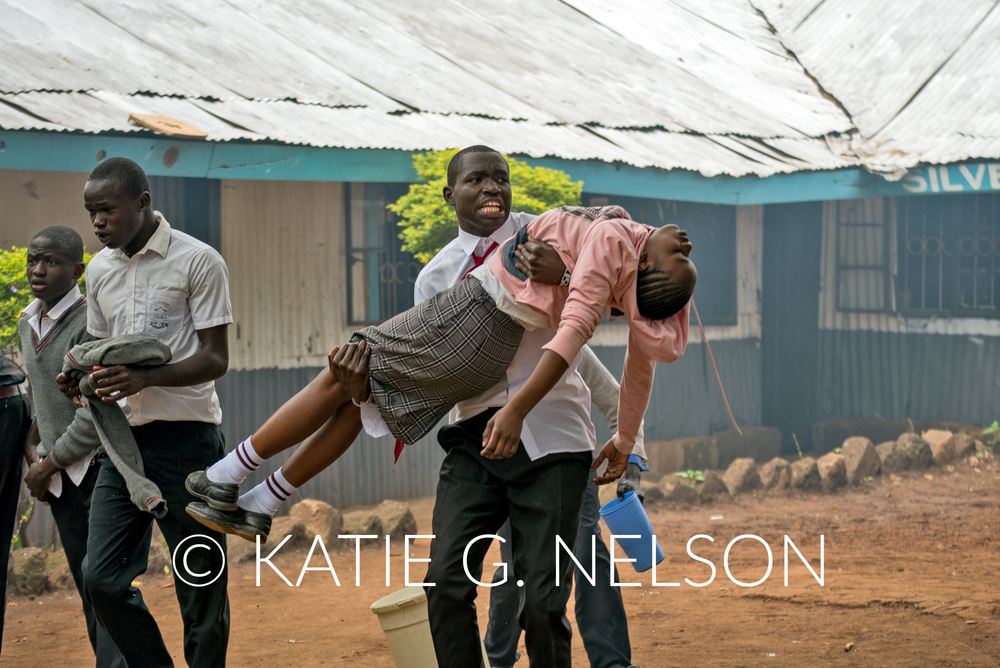A student carries his classmate out of the Silver Spring Secondary School after she collapsed inside her classroom.