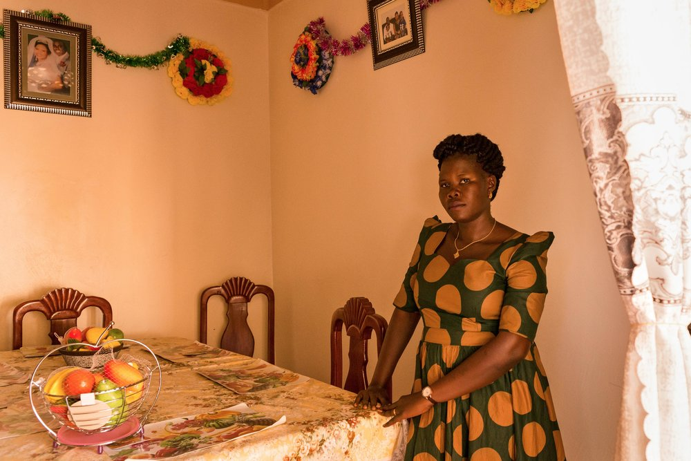 Lika, 29, stands at a dining room table in her home in northern Uganda.