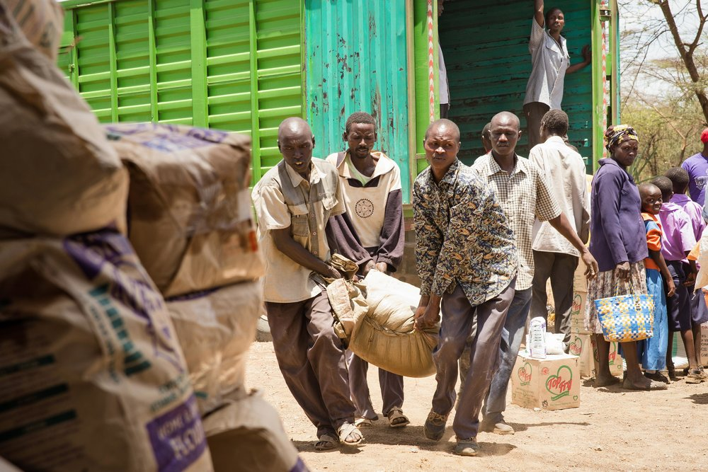 Men carry bags of beans and maize to a relief collection site in Baringo County, Kenya. Around 200 families collected food from the nonprofit Childcare Worldwide.