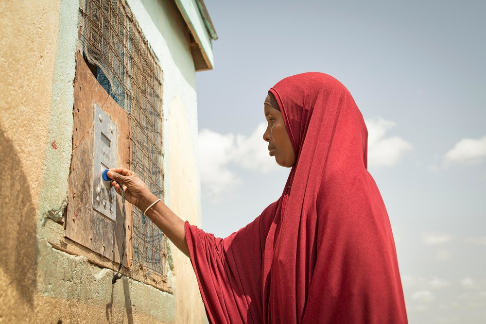 Arron Gesar, 34, holds her token to collect water from a Water ATM in Hadado, Kenya.