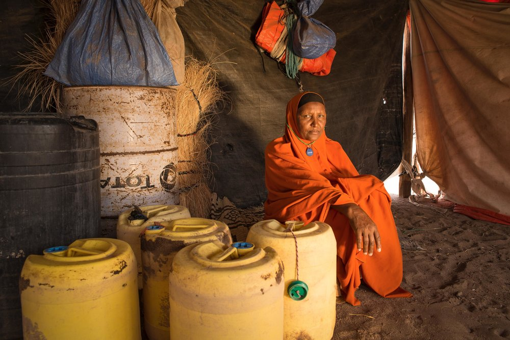 Bishara Abdi Iladir, 53, sits next to the Jerry Cans she uses to transport water from a pump to her home four times a day. The ongoing drought in the Horn of Africa forced Iladir's husband to take their livestock to lusher land in the east, leaving her 30 children and grandchildren without fresh milk, meat or a means to survive. It has been four months since her husband left; she hasn't heard from him since.