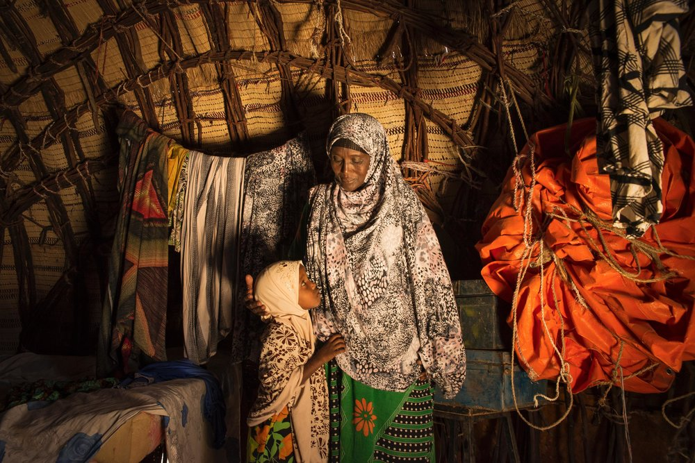Samey Alasow, 50, and her daughter sit inside their thatched-roof home in Hadado Town in Northern Kenya. The ongoing drought in the Horn of Africa forced Alasow's husband to take their livestock to lusher land in the east, leaving her and her daughter to fend for themselves in Hadado. That was eight months ago. They haven't heard from him since.