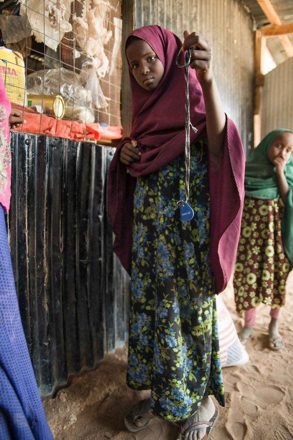 Sahara Ali Omar, 10, holds a water credit toiken outside a Water ATM top-up shop in Hadado town in Northern Kenya.