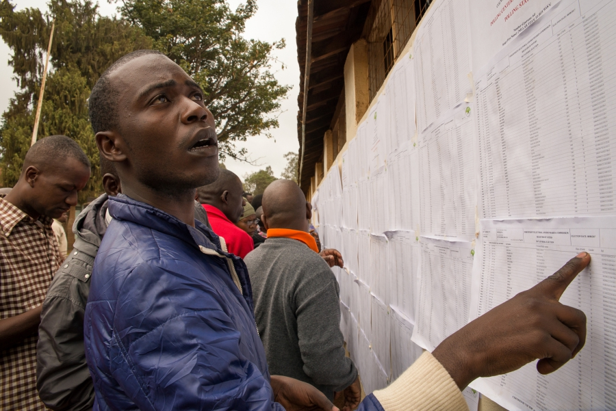 A man from an informal settlement in Nairobi searches for his name on a voter registration list at Kibera Primary School. Some voters were unable to locate their names on the registrar, forcing them to contact election officials for assistance. Katie G. Nelson