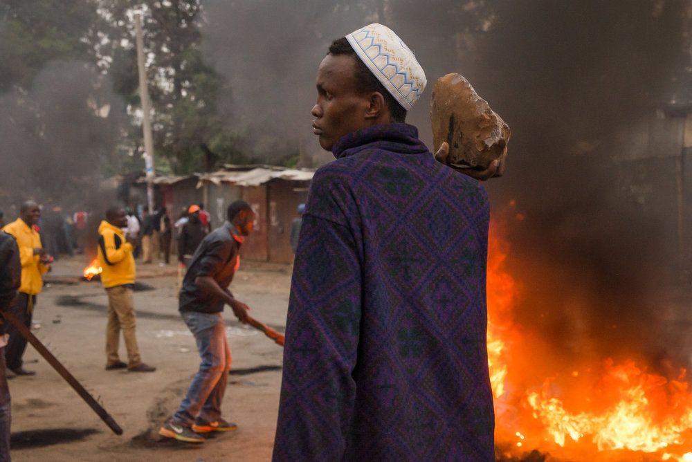 A man holds a large stone during a protest in Nairobi, Kenya. Credit: Katie G. Nelson/PRI