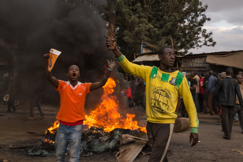 "Men yell ""Uhuru must go!"" during a demonstration in Kibera, an informal settlement of Nairobi, Kenya. Many of the residents support Raila Odinga of the National Super Alliance over current President Uhuru Kenyatta. Credit: Katie G. Nelson/PRI"