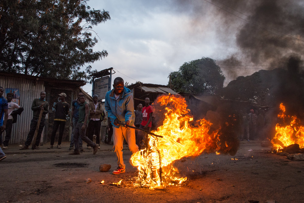 Men watch demonstrators light tires on fire in Nairobi's informal settlement of Kibera. The demonstration quickly turned violent as demonstrators armed themselves with stones and clubs bearing nails Wednesday evening. Credit: Katie G. Nelson/PRI
