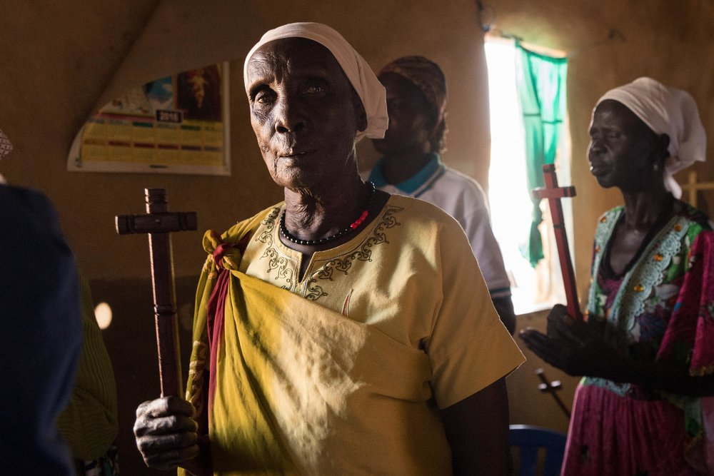 A Dinka woman holds a cross during a Protestant church service in Northern Uganda. Photo: Katie G. Nelson