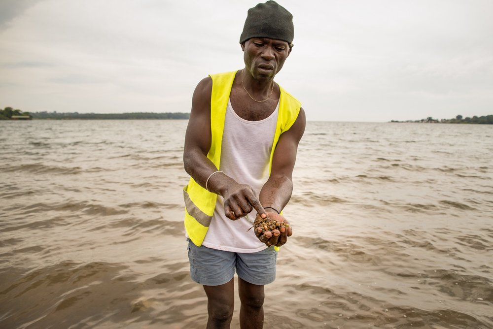Beach cleaner Bob Shaban with a handful of freshwater snails pulled from the banks of Lake Victoria in Uganda. These small snails often harbor the parasitic flatworm that transmits schistosomiasis. Photo: RTI International/Katie Nelson