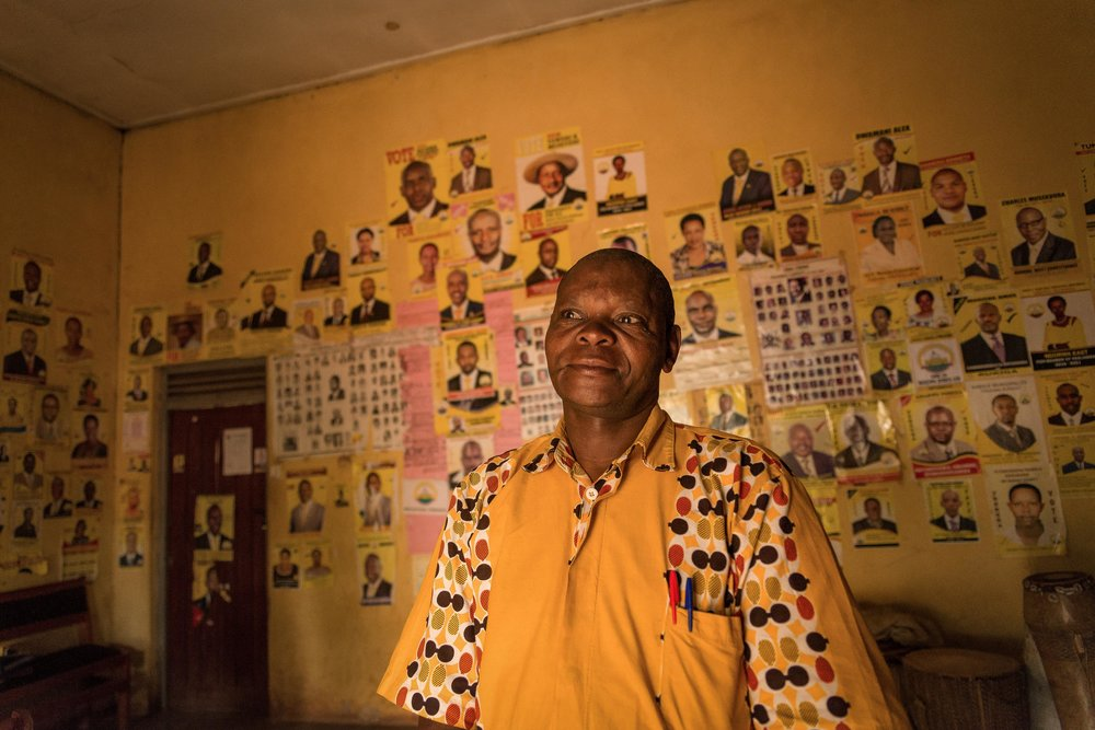 "Caleb stands against a backdrop of posters supporting the National Resistance Movement political party in southern Uganda in January 2018.  Deployed to northern Uganda when he was 19, the former solider said he ""killed many people"" while fighting in the Ugandan Bush War. ""But now, I'm saved,"" he said. ""I'm born again."" Caleb now works as a carpenter in southern Uganda.  From 1981 to 1986, Uganda was embroiled in a civil war that pinned President Apollo Milton Obote against rebel fighters led by current President Yoweri Museveni. Obote was ultimately overthrown by Museveni's National Resistance Army and replaced by Tito Okello.  Between 100,000 to 500,000 people died in Uganda as a result of the Ugandan Bush War. Both sides were responsible for widespread human rights abuse across the county."