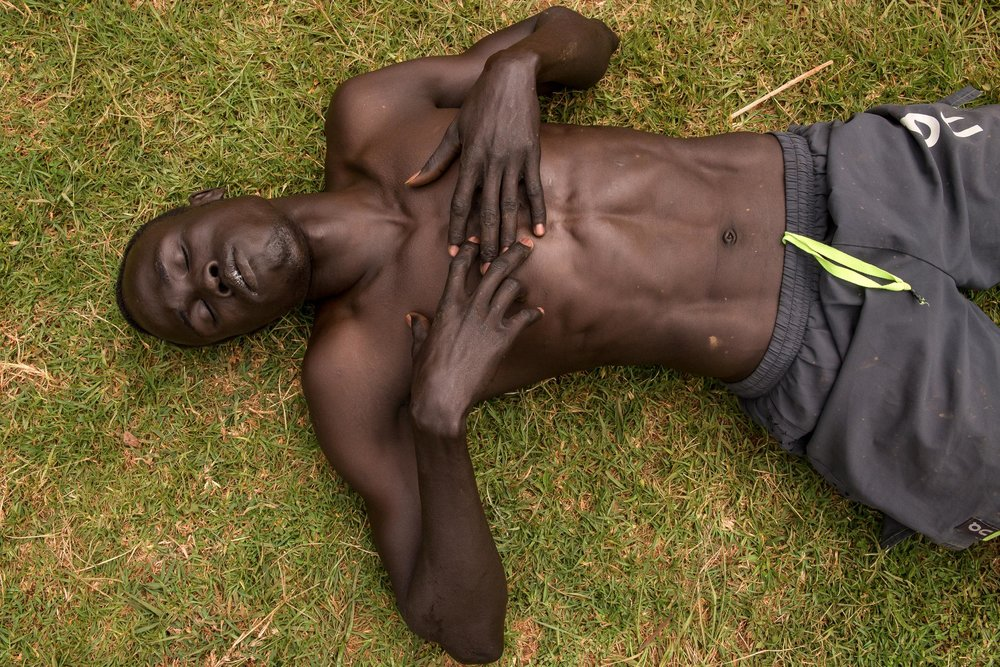 Wiyol, a short distance runner, collapses after morning training in Ngong Hills, Kenya.  Originally from South Sudan, Wiyol now runs with Team Refugee, a group of athletes from South Sudan, Ethiopia and Somalia who train in the high altitudes of Ngong Hills to prepare for international competitions like the Olympics.