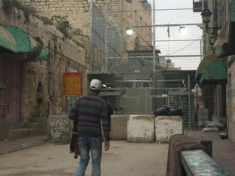 Matthew Williams/The Conflict Archives: A Palestinian civilian approaches a checkpoint in the city of Hebron.