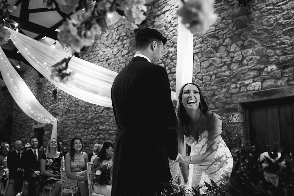 black and white photo of bride laughing during ceremony
