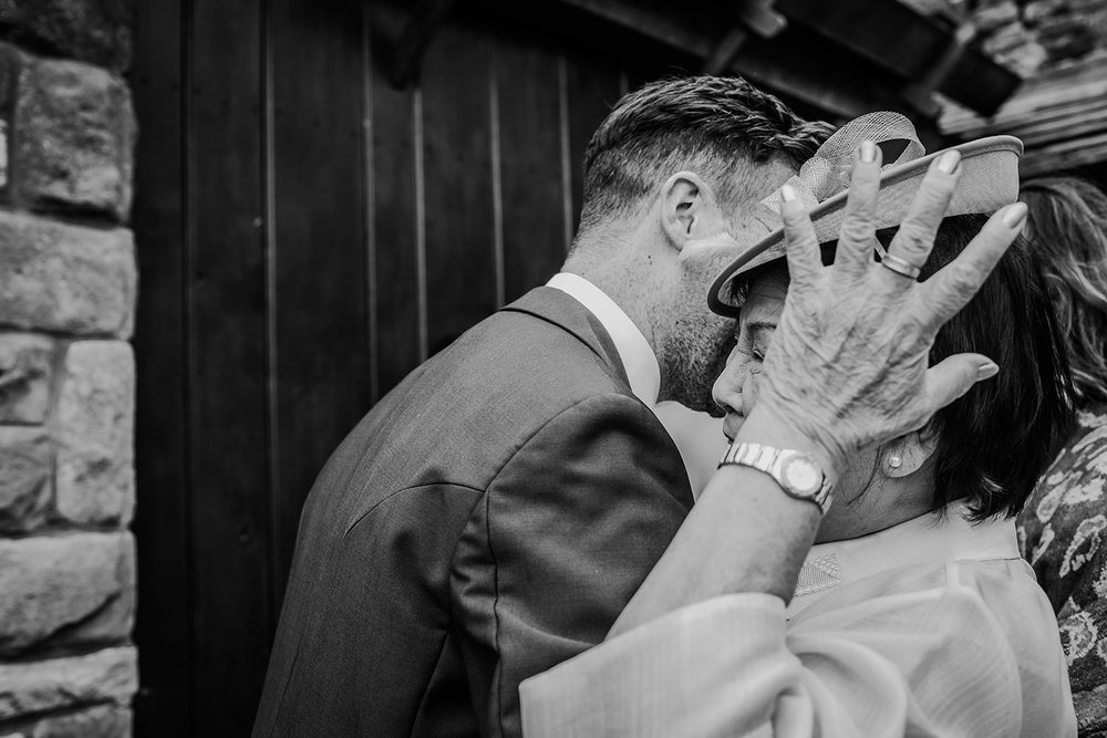 black and white photo groom hugging friend