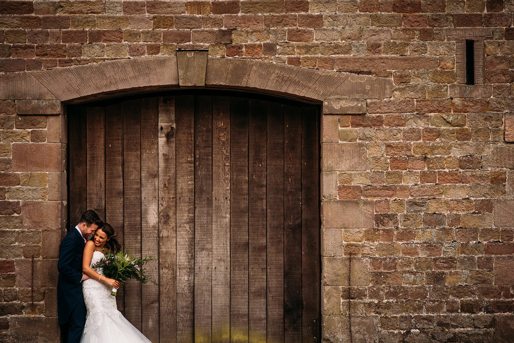 colour photo of bride and groom by barn door