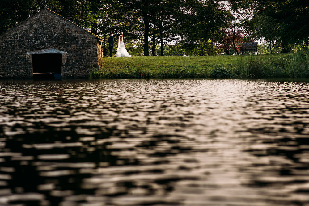 colour photo of bride and groom dancing by the lake