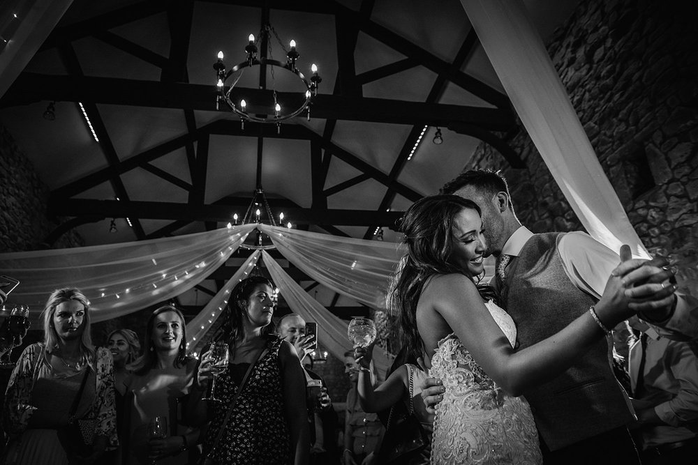 black white photo bride and groom dancing