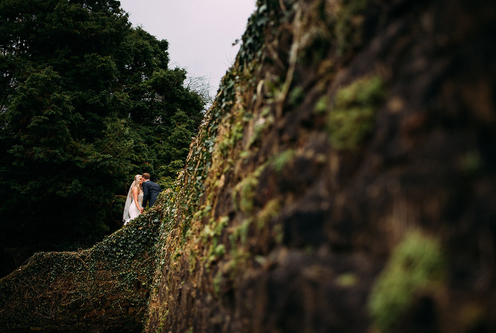 Bride and groom walking up garden stairs