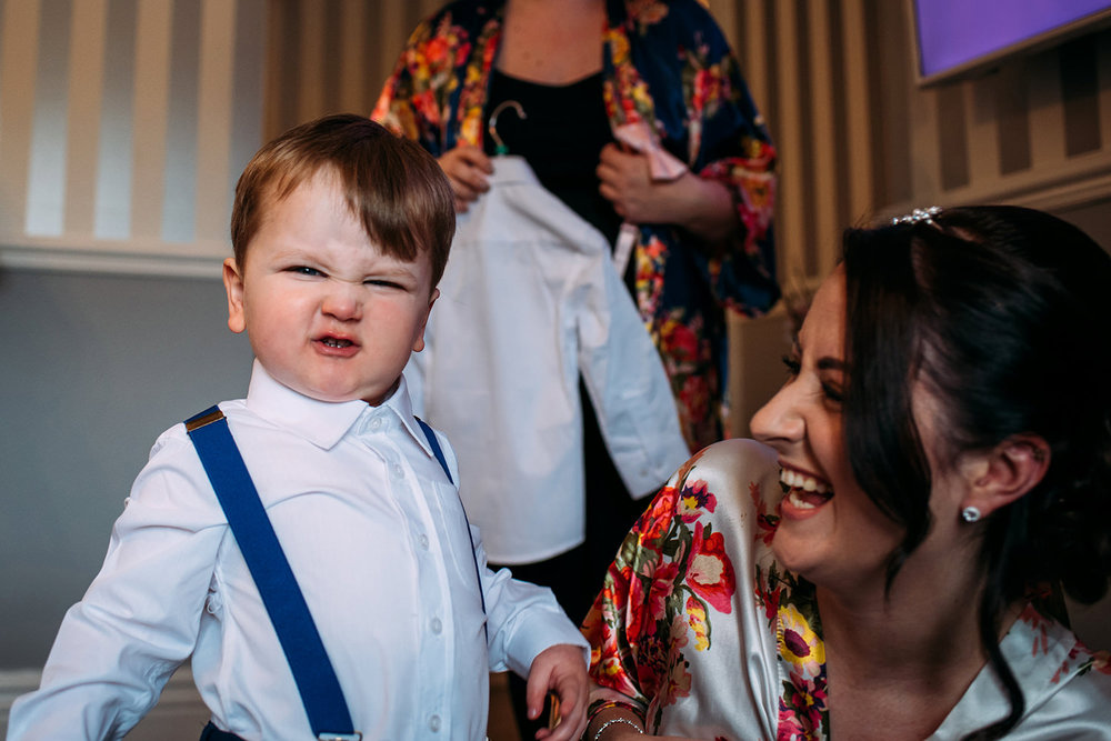 Bride and groom's son pulling his face at the camera