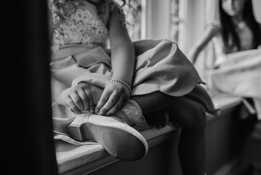 flower girl fastening shoe