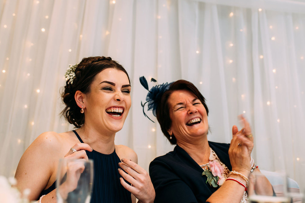 mother and sister of the groom laughing
