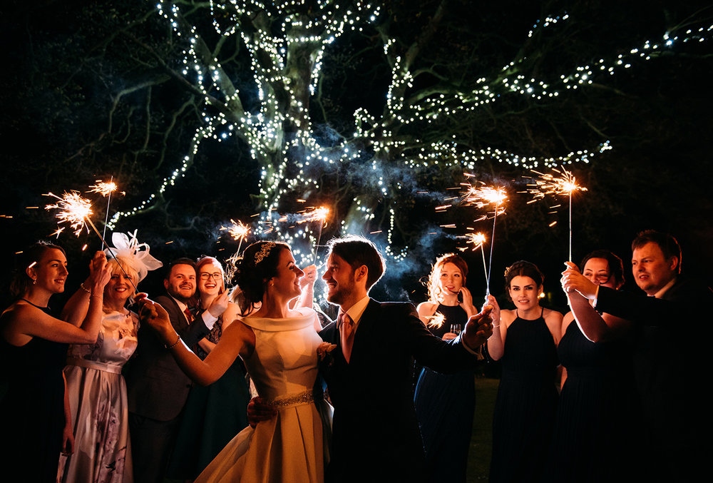 bride and groom with friends and sparklers