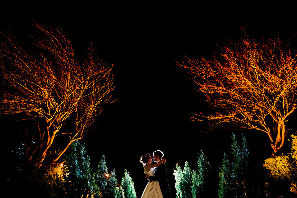 night time portrait of bride and groom kissing between two trees