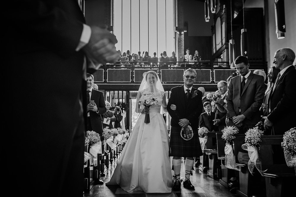 bride and father entering the church - groom waiting in the foreground