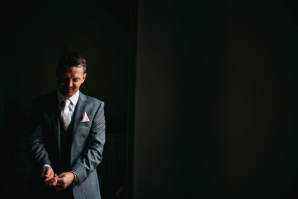 Groom adjusting sleeves and cuffs in window light