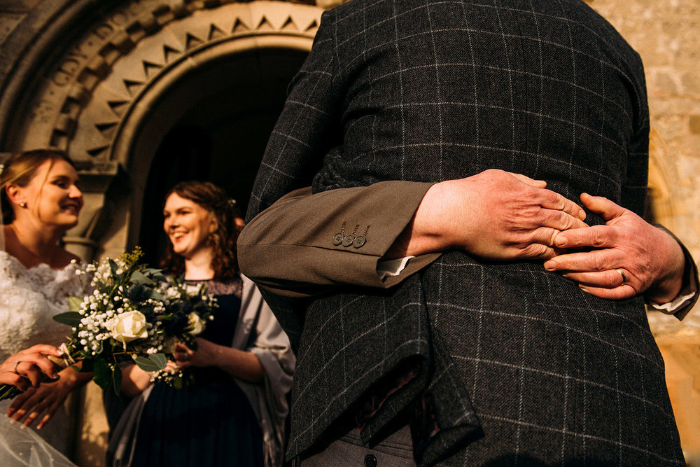 low angle shot over arms around the groom giving him a hug. Bride & bridesmaid in the background