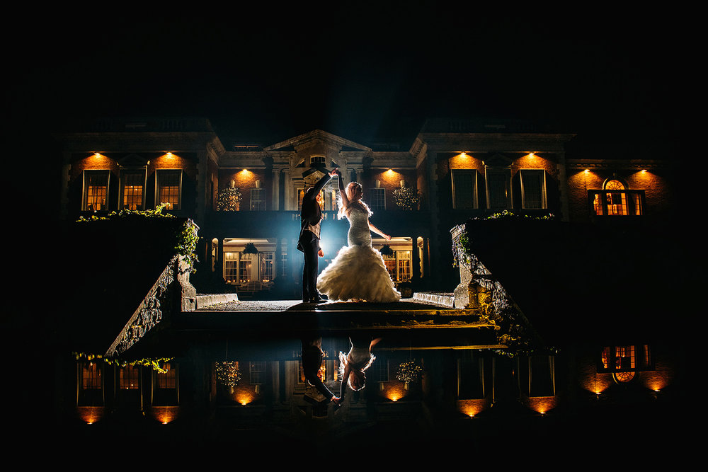 Bride and groom dancing in front of Eaves hall at night