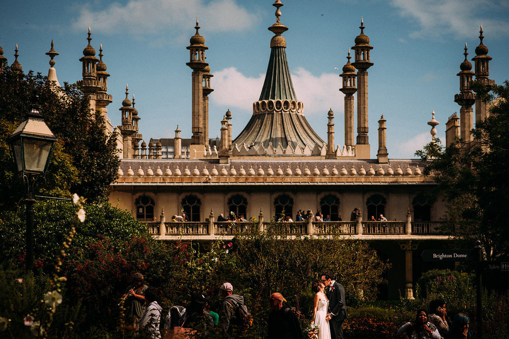 bride and groom kissing in front of Brighton Pavilion with people walking all around