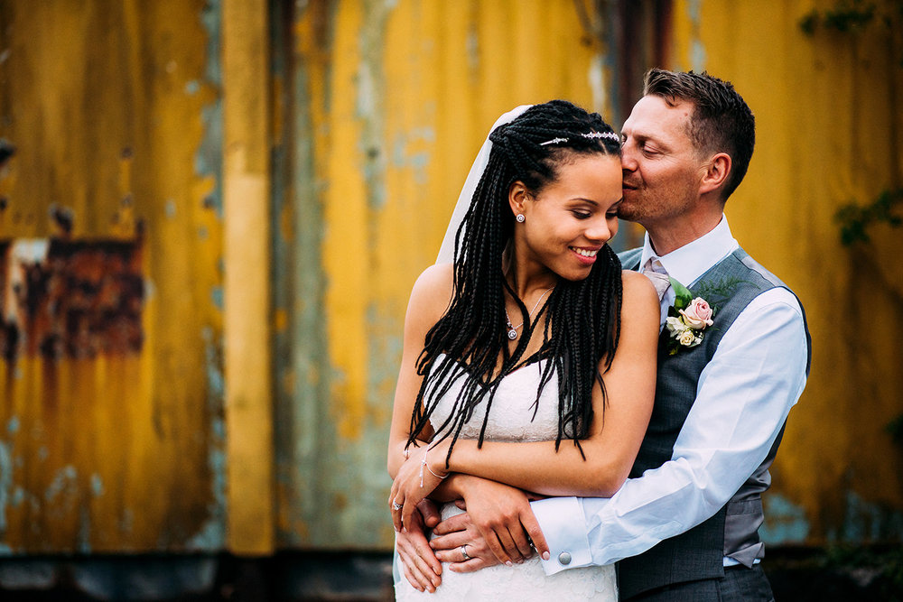 couple in front of a rusted yellow background