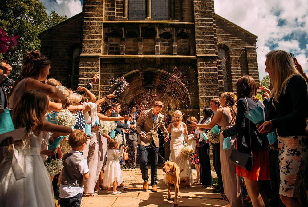 couple walking out of church through confetti with dog